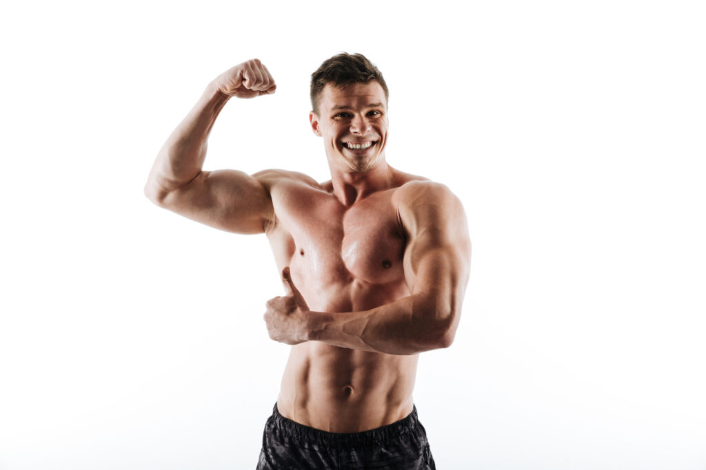 Muscular man smiling and flexing his bicep muscles